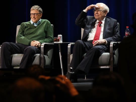 Bill Gates and Warren Buffett speak with journalist