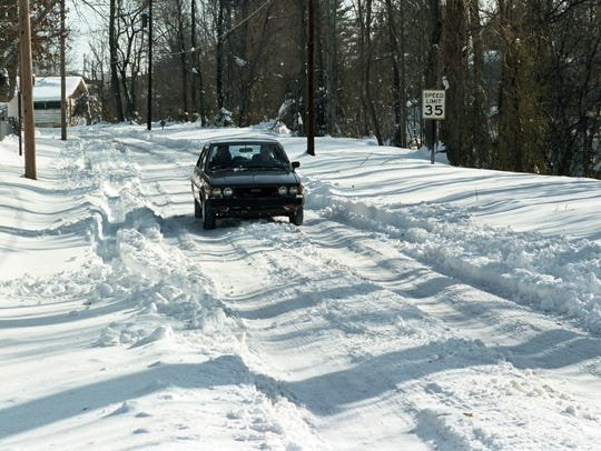A car negotiates a city street after the Blizzard of '93.
