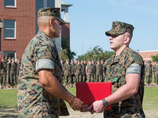 Marine Maj. Javier Garcia, left, presents the citation certificate to Sgt. Tyler Harman after pinning on the Navy & Marine Corps Achievement Medal during a ceremony at the Pensacola Naval Air Station on Thursday, April 12, 2018.  On February 1st, Harman saved his 2-year-old neighbor Rylan Strother's life when he was choking on a grape.