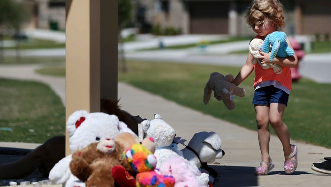 Judith McDuffie, 4, carries stuffed animals to place at a memorial with her mother Amanda McDuffie for the family that was murdered on Wednesday in the Remington Park neighborhood of Ponder, Texas, Thursday, May 17, 2018.