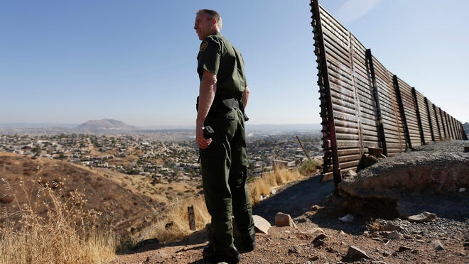 U.S. Border Patrol agent Jerry Conlin looks into Tijuana, Mexico, on June 13, 2013, along the old border wall at the base of a hill in San Diego.