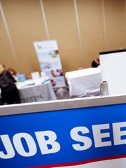 Employment seekers line the booths of job recruiters at a Job Fair.