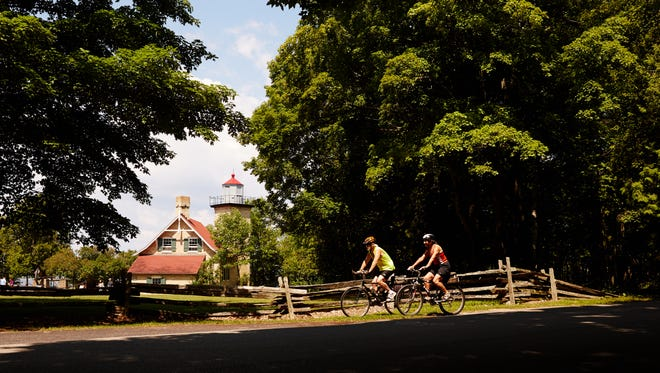 Bikers ride past Eagle Bluff Lighthouse in Door County's Peninsula State Park.