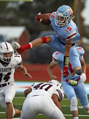Borden County tailback Ky Edwards (15) leaps over Rankin defensive lineman David Alvarado (40) during the Week Three contest on Friday at Coyotes Stadium in Gail.