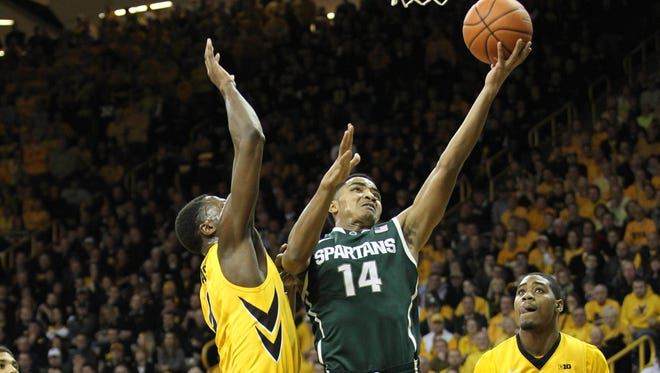 Iowa Hawkeyes forward Gabriel Olaseni defends Michigan State Spartans guard Gary Harris during the first half at Carver-Hawkeye Arena.