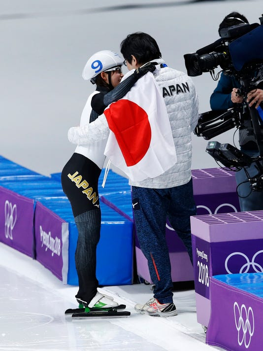 Gold medalist Nana Takagi of Japan is hugged by her coach as she celebrates with the national flag after the women's mass start final speedskating race at the Gangneung Oval at the 2018 Winter Olympics in Gangneung, South Korea, Saturday, Feb. 24, 2018. (AP Photo/Vadim Ghirda)