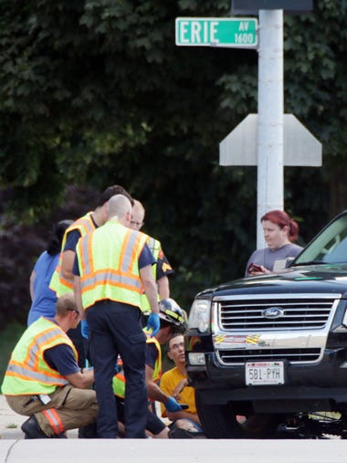 First responders talk to a male bicyclist who collided