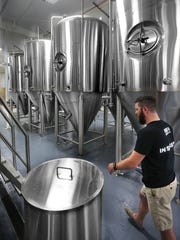 Jonathan Pacha walks past large fermenters inside the Proof Brewing Company on Friday. The Proof Brewing Company, one of Tallahassee's first breweries officially opened on Friday afternoon, May 16, 2014, at its facility at 644 McDonnell Drive in Railroad Square. Hundreds of people lined up for the grand opening and for the opportunity to sample a number of craft brews.