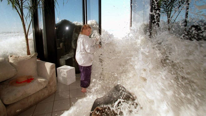Marilyn Lane attempts to close her doors to prevent a large wave from crashing into her Solimar Beach home near Ventura, Calif., on Jan. 30, 1998. Lane, whose house was one of several homes damaged by high surf in Ventura County, was sweeping water out the door from inside her home when a large wave came crashing in. The ubiquitous El Nino slammed into California, killing 17 and causing an estimated $550 million in damaged crops and property.