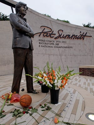 Flowers lay alongside a basketball fans have left at the Pat Summitt statue on the University of Tennessee campus Tuesday, June 28, 2016, in Knoxville, Tenn.