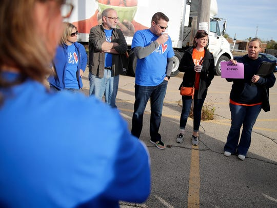 Carey Redmann, the member services manager for Feeding America Eastern Wisconsin-Northeastern Wisconsin, gives directions to volunteers on how much food they should give from each station before the Stock the Shelves mobile pantry Thursday, Oct. 19, 2017, in Appleton, Wis.