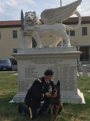 Lt. Col. Justin Schlanser poses with a military working dog in Italy just after Schlanser's promotion from major last summer. A veterinarian, Schlanser is a wildlife expert assigned to the U.S. Army's Africa command and plans to make several working trips to Africa next year.