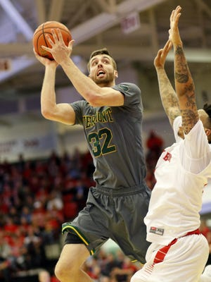 Vermont's Ethan O'Day puts up a shot while being defended by Stony Brook's Rayshaun McGrew in the America East championship game at Stony Brook, N.Y. on Saturday.