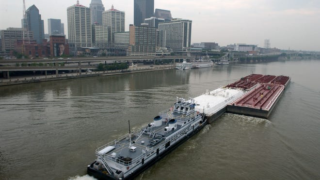 A barge goes down the Ohio River with the Louisville skyline in the background.  Photograph taken from the second street bridge.