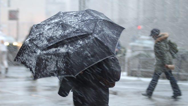 A pedestrian uses an umbrella to ward off wet snow.