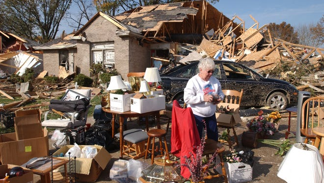 BOB GWALTNEY / Courier & Press ArchivesDorothy Rice organizes her belongings in her front yard as her house is filled with family and friends packing and cleaning inside to help salvage as much as they can. Rice and her husband Gerald were at home when the tornado hit and took refuge in an interior hallway As the house began to break apart she told how her husband threw her down on the floor and threw himself on top of her to protect her from the flying debris. He would have been little protection however, from the concrete block that came crashing through the roof missing their heads by inches .