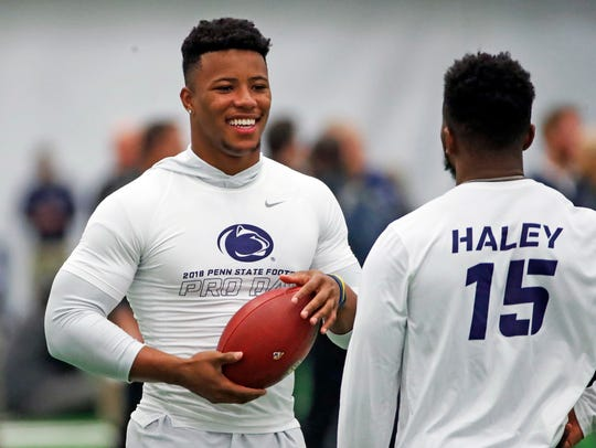Penn State running back Saquon Barkley, left, tosses