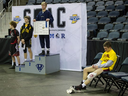 Mater Dei's Blake Boarman (right) holds up his second-place ribbon after injuring his knee against Castle's Devin Casebolt (middle right) in the title match of the 113-pound weight class.
