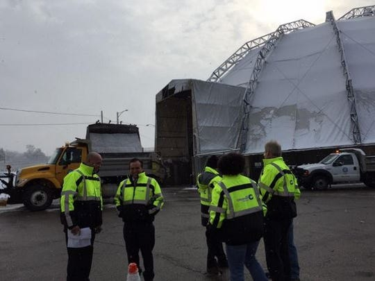 Crews load a salt truck behind city officials, as they prepare to conduct a press conference about the severe weather.