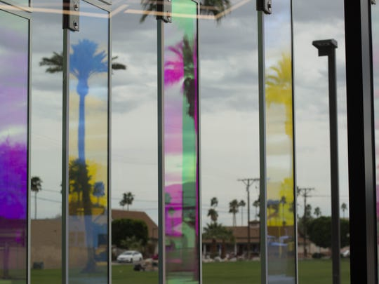 Colored glass panels mirroring palm trees in front of Loma Linda Children's Health Indio.