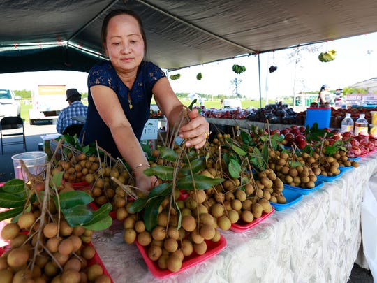 Ka Lee, of St. Paul, Minnesota, displays lychee fruit for sale at the 2018 Hmong Wausau Festival.