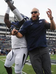 Nevada strength and conditioning coach Matt Eck meets defensive end Lenny Jones in the middle of the field before a game against Hawaii last Saturday.