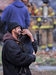 A man, who declined to give his name, having just lost almost all of his belongings in a house fire, reacts emotionally when his puppy is brought out of the burned house.