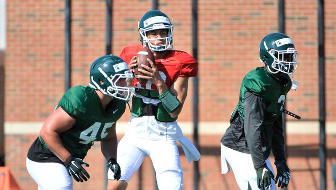 Quarterback Messiah deWeaver runs a drill at Michigan State football practice at the MSU practice field in East Lansing Wednesday.