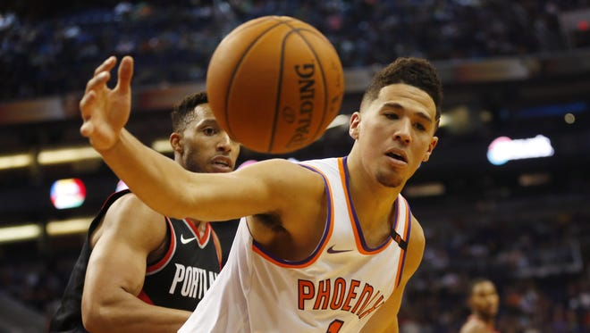 Phoenix Suns guard Devin Booker (1) recovers a ball while defended by Portland Trail Blazers guard/forward Evan Turner (1) during the third quarter at Talking Stick Resort Arena October 18, 2017.