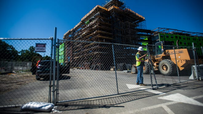 A worker closes a gate June 30 at UVM Central Campus where a construction worker fell to his death at the site of a new dorm.