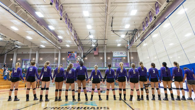 """Goshen College's women's volleyball team stands for the playing of """"America the Beautiful"""" before Wednesday's game against Saint Francis."""