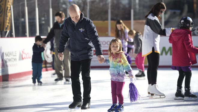 Scott Hamilton skates with Hanna Madson, 3, during a skate-a-thon earlier this year at the Bridgestone Winter Park outdoor ice rink in Nashville. Memphis will be getting an ice-skating rink this winter at Mississippi River Park, formerly known as Jefferson Davis Park.