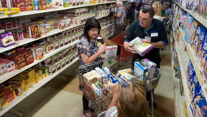 Volunteers stock shelves at United Against Poverty in Fort Pierce.