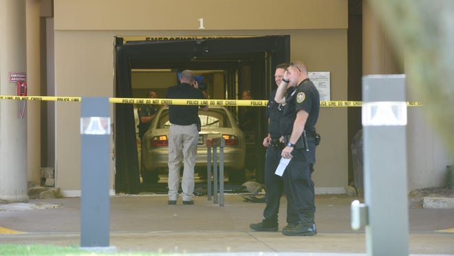Police investigate at Baxter Regional Medical Center Friday after a high speed pursuit suspect slammed through the hospital's emergency room doors. The suspect was captured and is undergoing medical treatment, according to authorities.