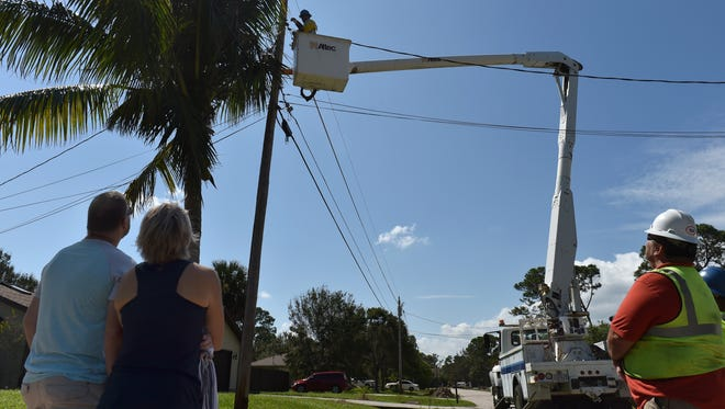 "James (left) and Noel McCormick anxiously watch as linemen from One Source Power, of Boston, reconnect the power line to their home in the 6000 block of Bamboo Drive on Sunday, Sept. 17, 2017 in the Indian River Estates development south of Fort Pierce. ""These guys are heroes,"" Noel McCormick said while watching the damaged power line repair from last weekend's Hurricane Irma. ""We have air conditioning; it's a beautiful thing."""