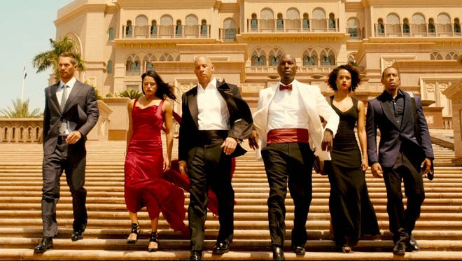 """The crew is back in action in """"Furious 7,"""" which is dedicated to the late Paul Walker (left)."""