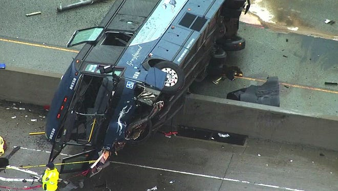 In this photo provided by KGO-TV, officials work at the scene of a fatal bus accident Tuesday, Jan. 19, 2016, in San Jose. The bus flipped on its side while traveling north on Highway 101, according to the San Jose Fire Department.