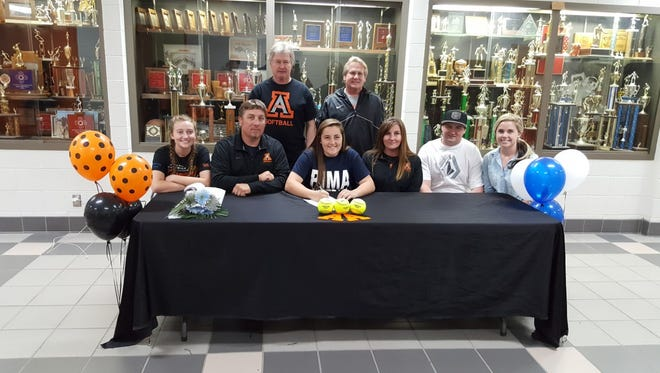 Paige Adair, center, signs a letter of intent to play softball for Pima Community College on Tuesday at Lillywhite Gym in Aztec.