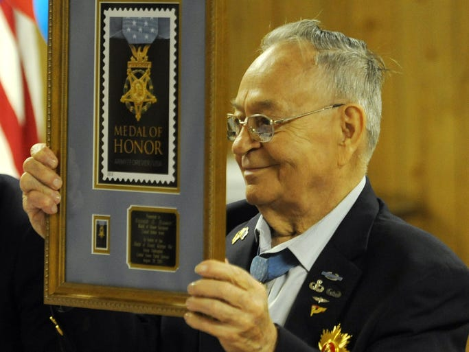 Ron Rosser shows the plaque presented to him by the United States Postal Service on Thursday during a ceremony in Roseville. Living winners of the Congressional Medal of Honor were invited to the unveiling of a stamp honoring winners of the medal this summer, but Rosser couldn't not attend because he was being honored by the Republic of South Korea with its Order of Military Merit.
