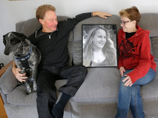 Jeff and his wife, Susan Shesto, and their dog Trigger, sit with a photo of their daughter, Sophie, that was on display at Sophie's memorial service after she died of a heroin overdose on June 28, 2015, at their home in Milwaukee.