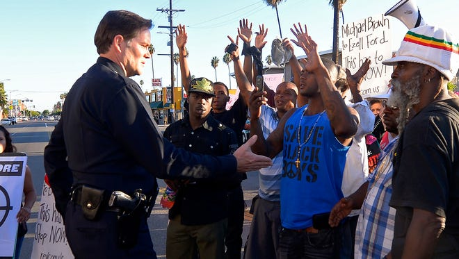 FILE - In this Aug. 14, 2014 file photo, protesters hold their hands up as a Los Angeles Police Department officer tries to talk to them in front of the 77th Street police station in Los Angeles during a protest of the LAPD shooting of Ezell Ford. Police say that Ford had attempted to remove a gun from an officer's holster on Monday when he was shot and killed, which differs from accounts by the family of the man. Details may differ, circumstances of their deaths may remain unknown, but the outrage that erupted after the Aug. 9 fatal shooting of the unarmed, black 18-year-old by a white officer in Ferguson, Missouri, has become a rallying cry in protests over police killings across the nation. (AP Photo/Mark J. Terrill, File)