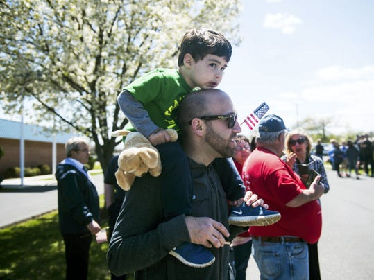 Carter Rome, 3, keeps an eye to the Allstar complex entrance as he and his dad, Brett Rome, both of Rockville, Md, wait for the bike riders to come through the finish line on April 26, 2015. Clare Becker - The Evening Sun