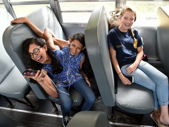 Carmen and Lupita Andrade, left, laugh with friends on the bus after a day at Nonnewaug High School in Woodbury where they are enrolled in the agriscience program. They hope for a career in large animal veterinary medicine. Maddie Wuttke, right, is a freshman in the agriscience program.