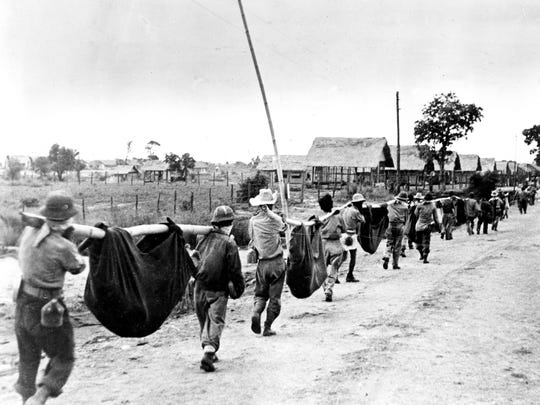 Nearing the end of the Bataan Death March, a thinning line of American and Filipino prisoners of war carry casualties in improvised stretchers as they approach Camp O'Donnell, a new Japanese POW camp, in April 1942 during World War II.