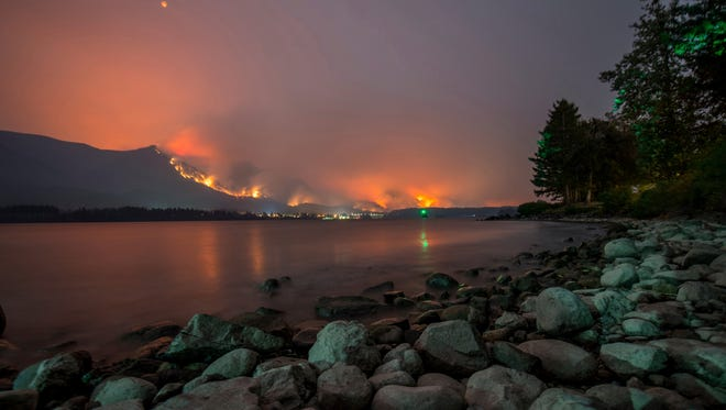 This Monday, Sept. 4, 2017, photo provided by KATU-TV shows a wildfire as seen from near Stevenson Wash., across the Columbia River, burning in the Columbia River Gorge above Cascade Locks, Ore. A lengthy stretch of highway Interstate 84 remains closed Tuesday, Sept. 5, as crews battle the growing wildfire that has also caused evacuations and sparked blazes across the Columbia River in Washington state.