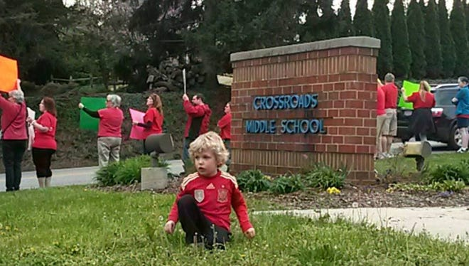 Matthew Gonce, 3, picks dandelions outside Crossroads Middle School while his mother, Alison Gonce, joins fellow West Shore Education Association teachers in protest in April. Photo by John Joyce