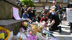 Police officers relocate tributes in St Ann's Square