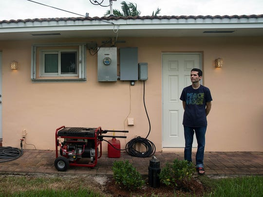 Cristian Seiglie, 44, stands next to the generator