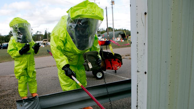 The 388th Chemical Biological Radiological Nuclear Company's hazmat reconnaissance soldiers practice determining the chemical at play during a training exercise with local authorities at the Stevens Point Municipal Airport, Saturday.