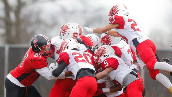 William Penn's Titus Nelson (obscured) draws a crowd to bring him to the ground during Smyrna's 30-13 Division I semifinal win last Saturday.